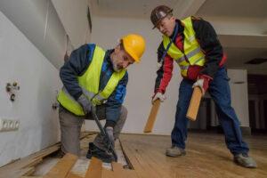 Bauarbeiter beim Holzbodenplatten entfernen