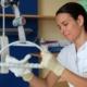Frau putzt mit Desinfektionsmittel Krankenhausbett