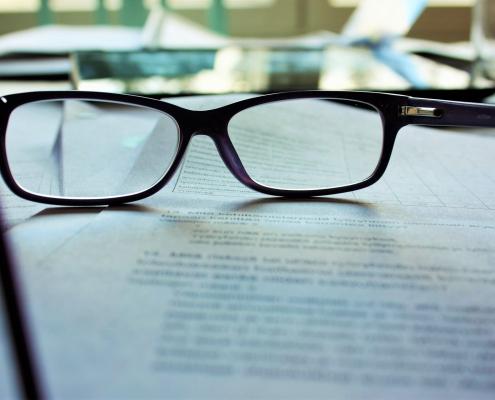 Brille auf schriftlichen Unterlagen